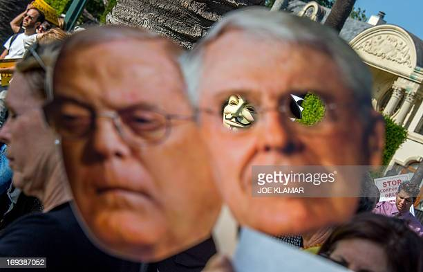 Protesters attend a rally and march demanding Los Angeles Times not be sold to the Koch Brothers portraits of which are held May 23 2013 in Beverly...