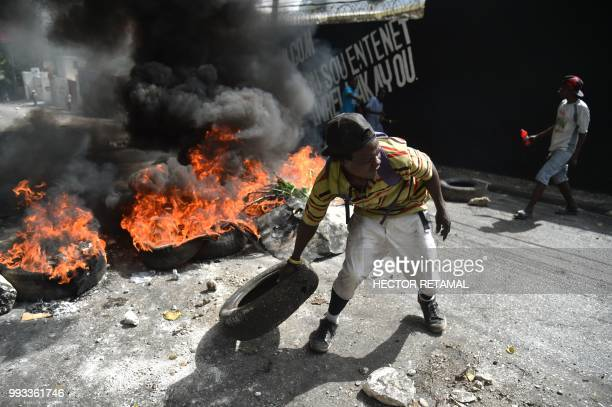 TOPSHOT Protesters barricade a street in the PortauPrince suburb of PetionVille on July 7 to protest against the increase in fuel prices Haiti's...
