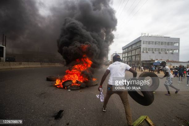 Protesters barricade the road with burning tyres during a anti-government demonstration in Luanda on October 24, 2020. - Angolan anti-riot police,...
