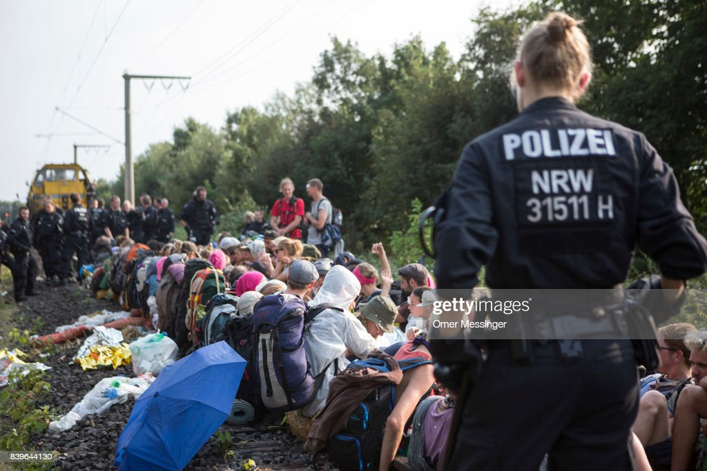 Protesters block a rail track as German policemen surround them in the Rhineland (Rhenisch) mines region west of Cologne on August 26, 2017 near the German village of Rath, Germany. Protesters seeking to bring attention to the impact of coal on climate change have converged on the region for two days of disruptive disobedience. The mines, which include the Hambach, Garzweiler, Inden and Bergheim mines, are operated by German utility RWE and produce lignite coal.