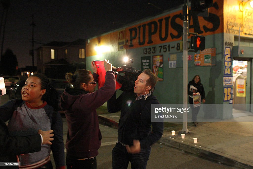 Protesters block a television news crew trying to cover a rally at the site where Ezell Ford, a 25-year-old mentally ill black man, was shot and killed by two LAPD officers in August, on December 29, 2014 in Los Angeles, California. The long-awaited autopsy report, which was put on a security hold at the request of police and ordered by L.A. Mayor Eric Garcetti to be made public before the end of 2014, was released December 29.