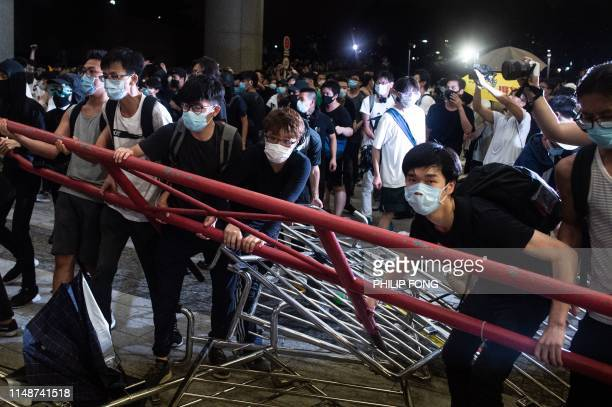 TOPSHOT Protesters block the protest area of Legislative Council with barricades during clashes with police after a rally against a controversial...