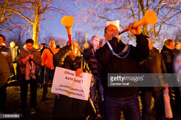 Protesters blow into vuvuzelas outside Bellevue Palace during the Zapfenstreich or taps farewell ceremony taking place in the Bellevue garden on...