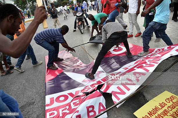 Protesters break an election poster of the presidential candidate Jovenel Moise during a march in PortauPrince on December 16 to protest against the...