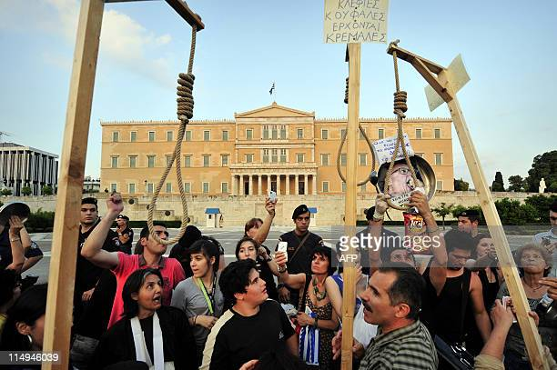 Protesters bring symbolic gallows 'to hang the politicians' in front of the Greek Parliament on May 30, 2011 during their gathering for the sixth...