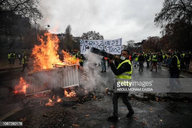Protesters build a barricade during a protest of Yellow vests against rising oil prices and living costs, on December 1, 2018 in Paris.