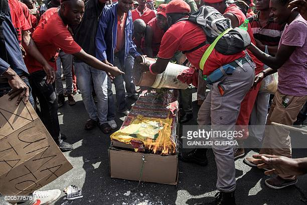 Protesters burn a cardboard mock up coffin with the picture of South African President Jacob Zuma as Members and supporters of the South African...