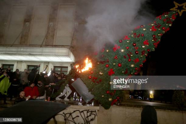 Protesters burn a Christmas tree in front of the Albanian Prime Minister building during clashes in Tirana on December 9, 2020. - Albanian police...
