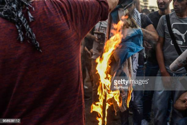 Protesters burn a flag of Israel outside the Israeli embassy during a demonstration in central Athens on May 15 2018 against the bloodshed along the...