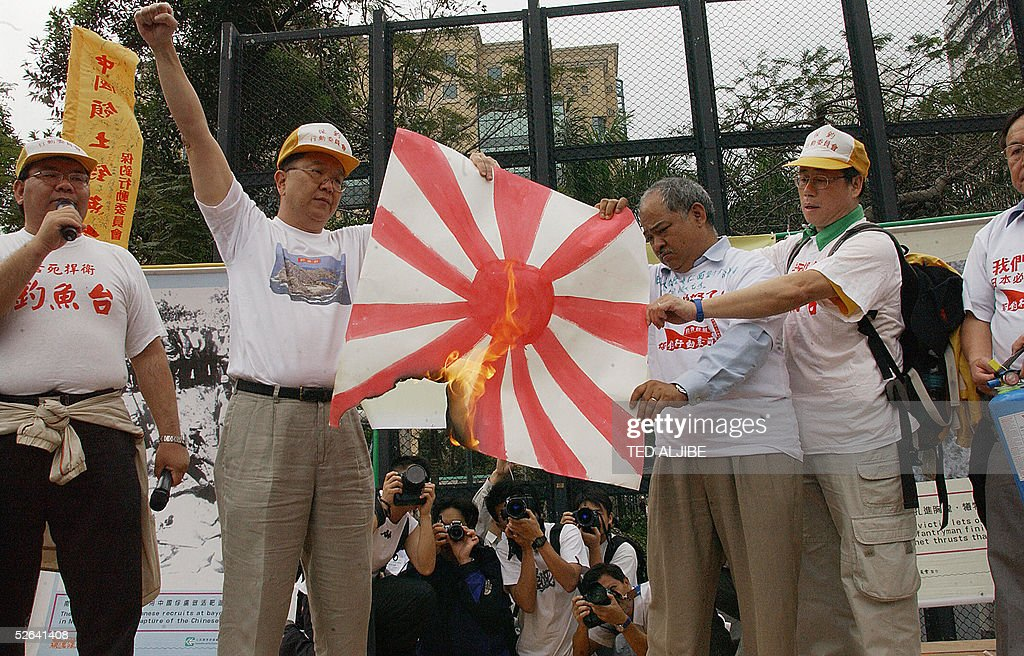 Protesters burn a Japanese imperial flag prior to the start