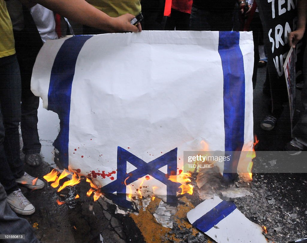 Protesters burn a paper Israeli flag during a protest in front of the building housing the Israeli embassy in the financial district of Manila on June 2, 2010. Activists in the Philippines on June 2, strongly condemned what they called a brutal attack by Israel on a Gaza-bound aid flotilla that left nine people dead.