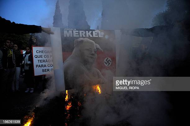 Protesters burn a placard depicting Angela Merkel as a pig with a Nazi swastika symbol during protest against the visit of German Chancellor Angela...
