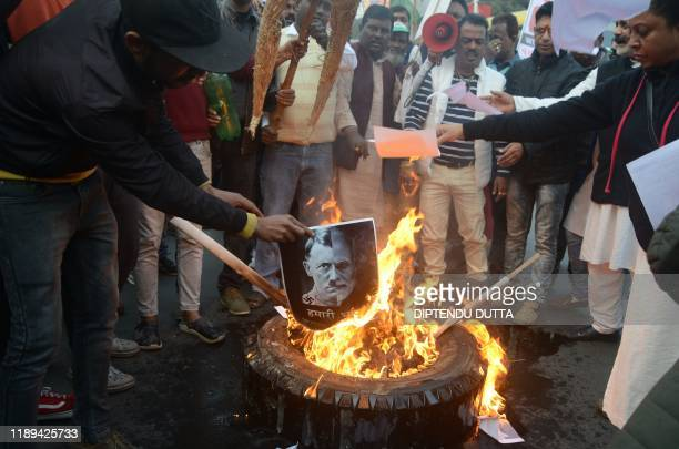 Protesters burn a poster comparing Indian Prime Minister Narendra Modi to German chancellor and Nazi Party leader Adolf Hitler at a demonstration...