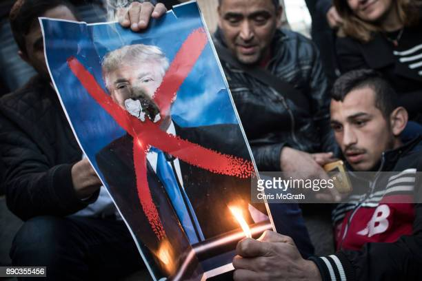 Protesters burn a poster of US President Donald Trump in front of the Damascus Gate at the entrance to the Old City on December 11 2017 in Jerusalem...