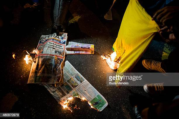 Protesters burn a Tshirt and newspapers with news of the Brazilian national football team during a demonstration against the 2014 FIFA World Cup...