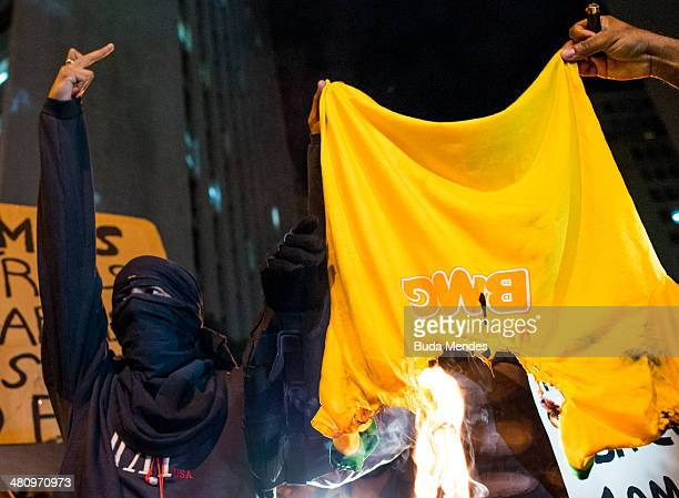 Protesters burn a Tshirt of the Brazilian national football team during a demonstration against the 2014 FIFA World Cup Brazil at Central do Brasil...