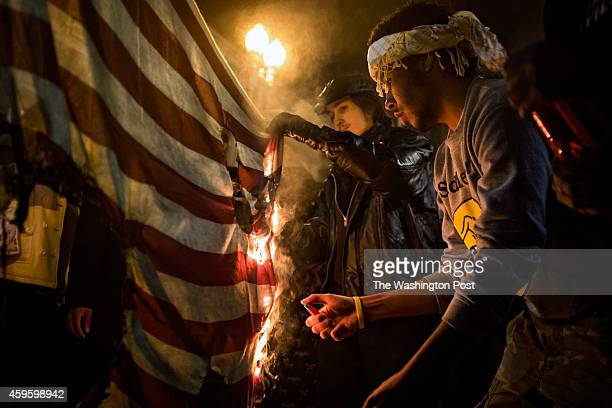 Protesters burn a US flag as they march through downtown Washington DC following a Missouri grand jury's decision not to indict Officer Darren Wilson...