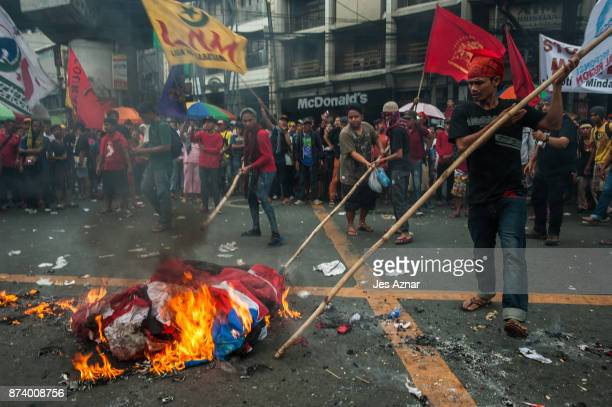 Protesters burn a US flag to protest US President Trump's visit in the Philippines on November 14 2017 in Manila Philippines Hundreds of Filipinos...