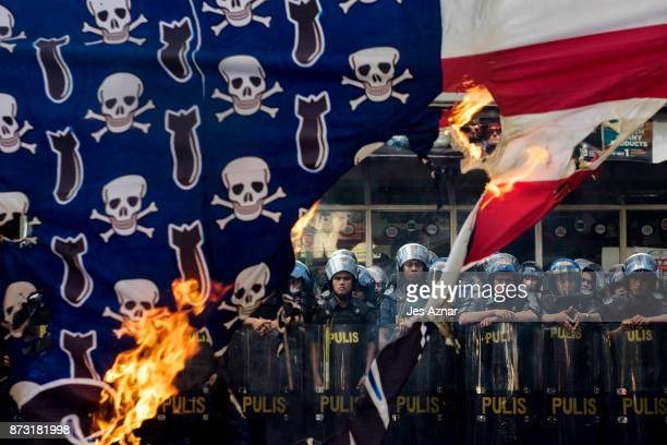 Protesters burn an Amercian flag as they march in the streets of Manila on the day of US President Trump's arrival on November 12 2017 in Manila...