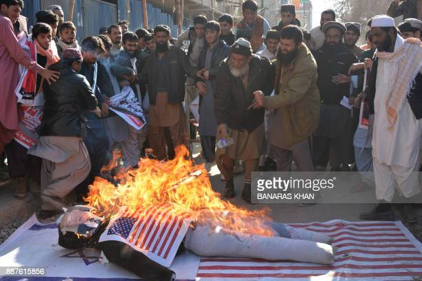 Protesters burn an effigy depecting US President Donald Trump during an antiUS and Israeli protest in Quetta on December 7 2017 following Trump's...