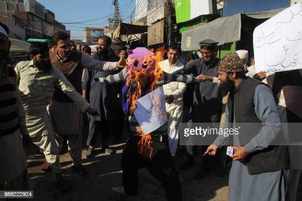 Protesters burn an effigy depecting US President Donald Trump during an antiUS and Israeli protest in Multan on December 8 following Trump's decision...
