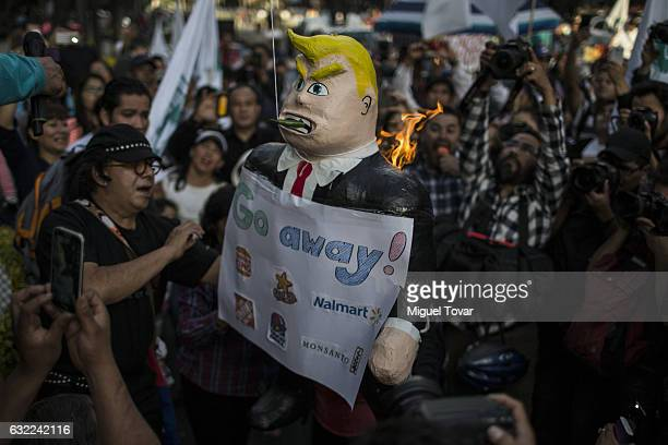 Protesters burn an effigy of Donald Trump during protest against US President Elect Donald Trump after being sworn in at Mexican US Embassy on...