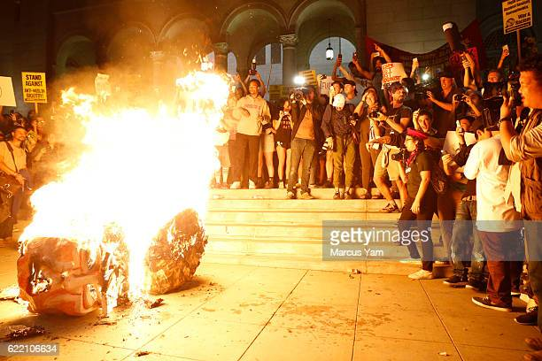 Protesters burn an effigy of Donald Trump outside Los Angeles City Hall