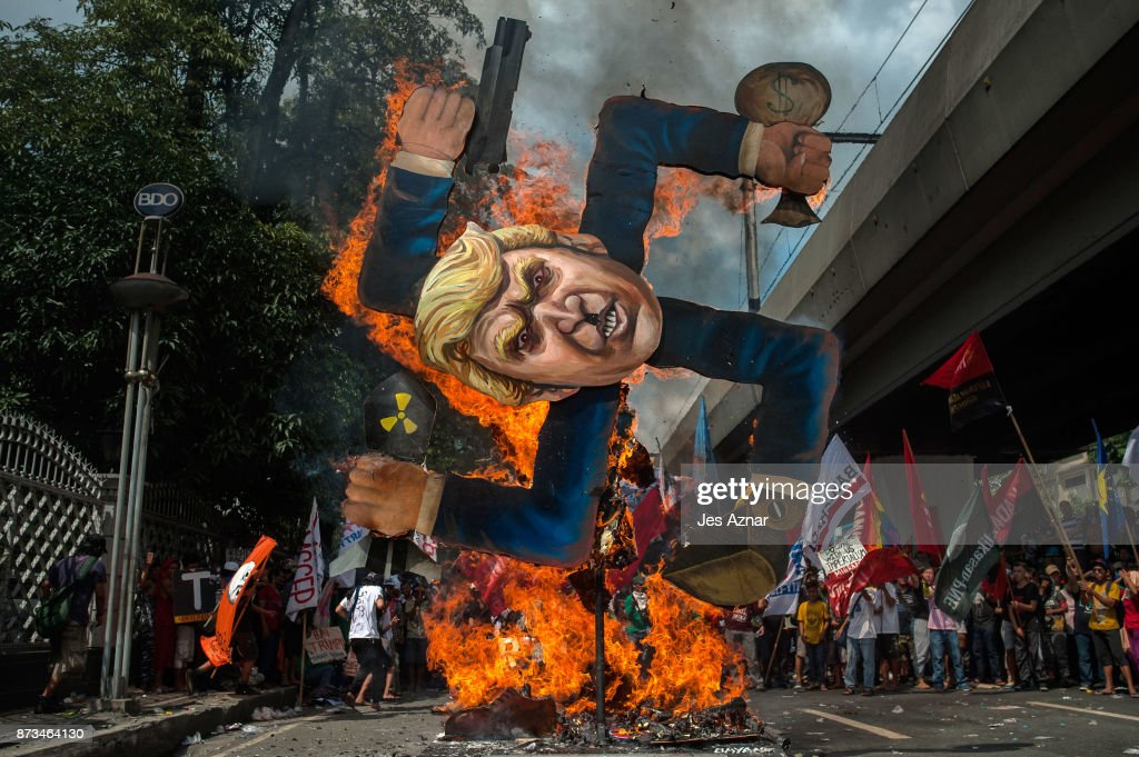 Protesters burn an image of US President Donald Trump fashioned on a swastika as they march the streets of Manila during the start of the ASEAN meetings between heads of state on November 13, 2017 in Manila, Philippines. Thousands of Filipinos protested in Manila as U.S. President Donald Trump's attended the ASEAN meetings in the Philippines, a stop included in his 12-day Asia trip.
