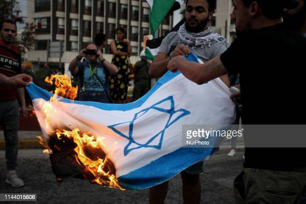 Protesters burn an Israeli flag and shout slogans during a protest rally by Palestinians outside the embassy of Israel in Athens Greece on May 15...