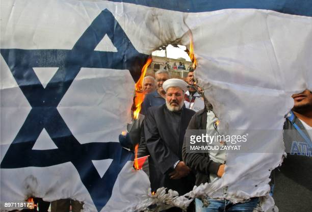 TOPSHOT Protesters burn an Israeli flag during a demonstration organized by Hezbollah in the streets of the southern Lebanese port city of Sidon on...