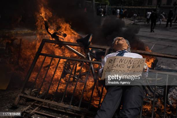 Protesters burn barricades as they gather to march on the sixth day of social riots for increases in public transport in Santiago of Chile on October...