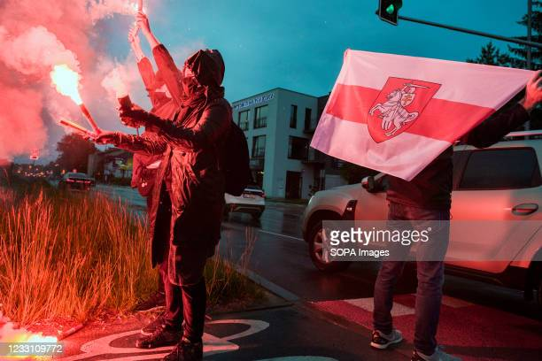 Protesters burn flares and wave the forbidden historical Belarusian flag during the protest. Belarusians residents in Poland gathered outside the...