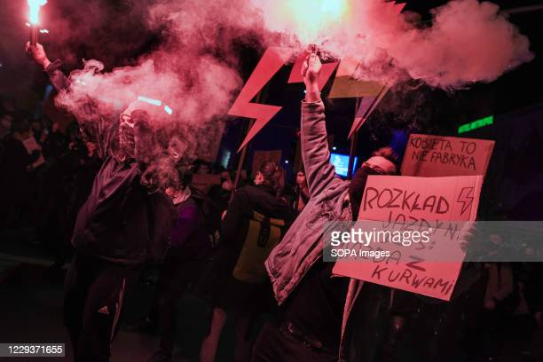 Protesters burn flares while chanting anti-government slogans during the demonstration. Tens of thousands of people took to the streets of Poland for...
