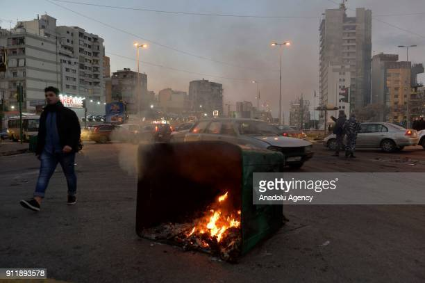 Protesters burn garbage bin used as a road block during a protest to condemn libelous video about Lebanese Parliament Speaker Nabih Berri in Beirut...