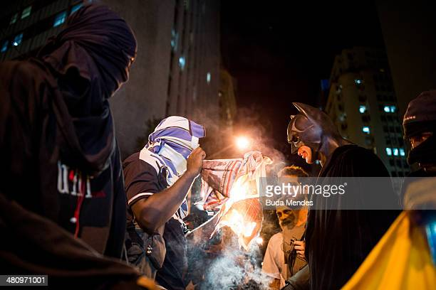 Protesters burn newspapers with news of the Brazilian national football team during a demonstration against the 2014 FIFA World Cup Brazil at Central...