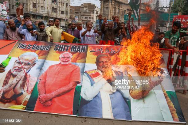 TOPSHOT Protesters burn pictures of Indian Prime Minister Narendra Modi during a protest in Hyderabad on August 15 as the country observes 'Black...