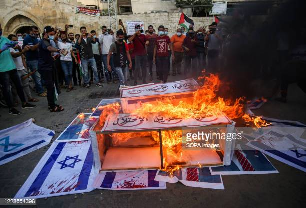 Protesters burn placards during the demonstration. Palestinians protest against the Israeli normalization agreement with the UAE and Bahrain in Khan...