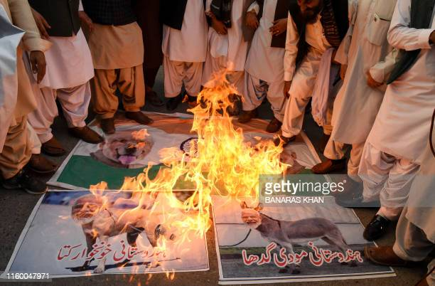 Protesters burn posters featuring images of Indian Prime Minister Narendra Modi during a protest in Quetta on August 6 a day after India stripped the...