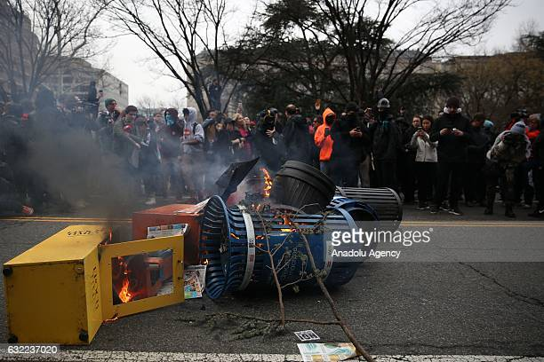 Protesters burn the garbage pins during the protest against the 45th President of the United States Donald Trump in Washington USA on January 20 2017