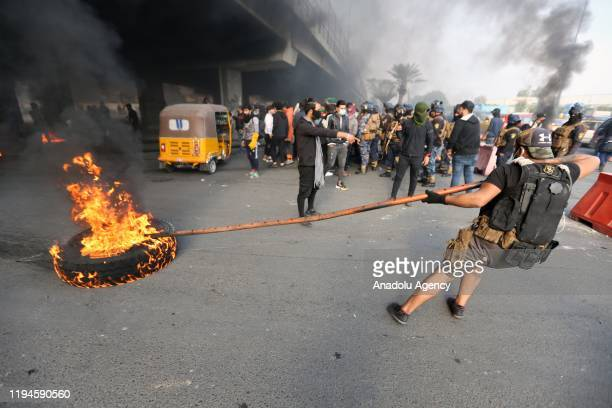 Protesters burn tires to block the road during the anti-government demonstration at al-Tayaran Square in Baghdad, Iraq on January 19, 2020.