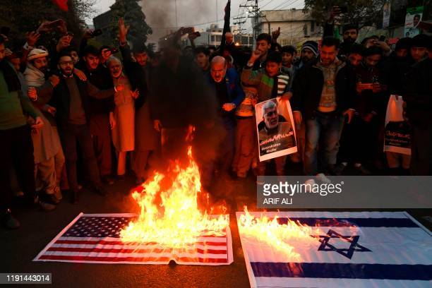 Protesters burn US and Israel flags as they shout slogans against the United States during a demonstration following a US airstrike that killed top...