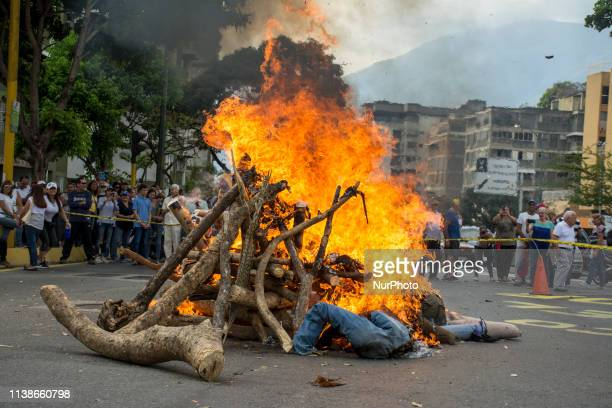 Protesters burned dolls stuffed with rags and bills representing Nicolas Maduro and other members of his government in Caracas Venezuela on 22 April...