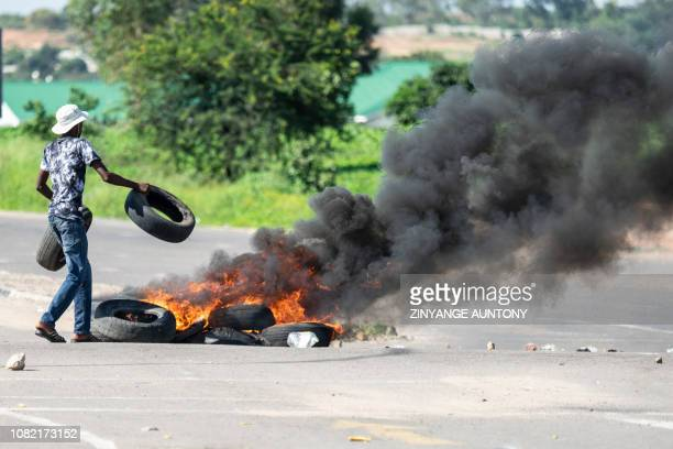 A protesters burns tyres on a road during a stayaway demonstration against the doubling of fuel prices on January 14 2019 in Emakhandeni township...