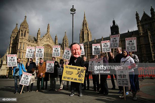 Protesters call for prison sentences for tax evaders outside parliament on February 25 2015 in London England