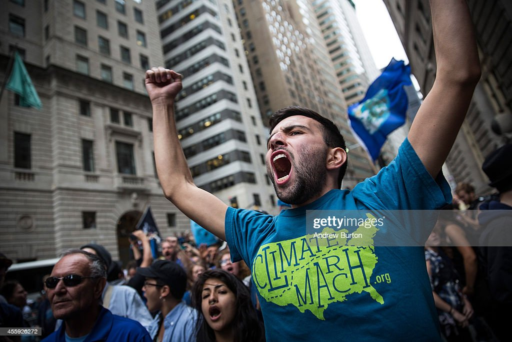 Protesters calling for massive economic and political changes to curb the effects of global warming hold a sit in around the Wall Street Bull statue on Broadway on September 22, 2014 in New York City. Approximately 2,600 protesters participated; despite blocking traffic on numerous streets few arrests have taken place.