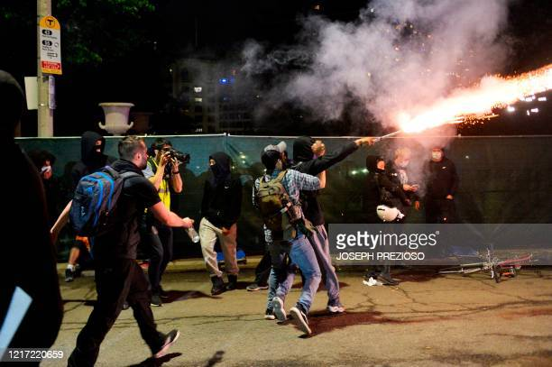Protesters calling for peaceful actions tackle a protester who launched fireworks at the olice by the steps the State House to protest the death of...