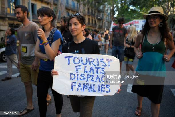 A protesters carries a banner that reads 'Tourist flats displace families'during a demonstration in Barcelona on June 10 2017 against what they claim...