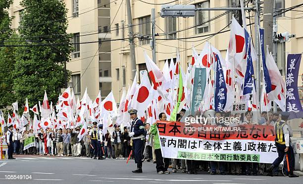 Protesters carry a banner and national flags during an antiChina demonstration march in central Tokyo on October 16 2010 Japanese national flags...