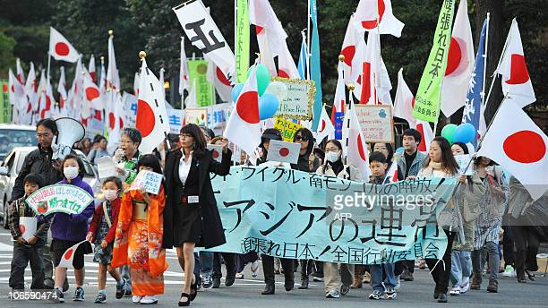 Protesters carry a banner and national flags during an antiChina demonstration march in central Tokyo on November 6 2010 Japanese national flags...