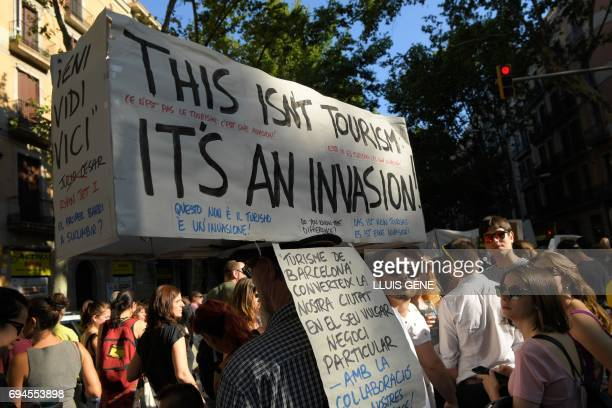 Protesters carry a banner that reads 'This isn't tourism it's an invasion' during a demonstration in Barcelona on June 10 2017 against what they...